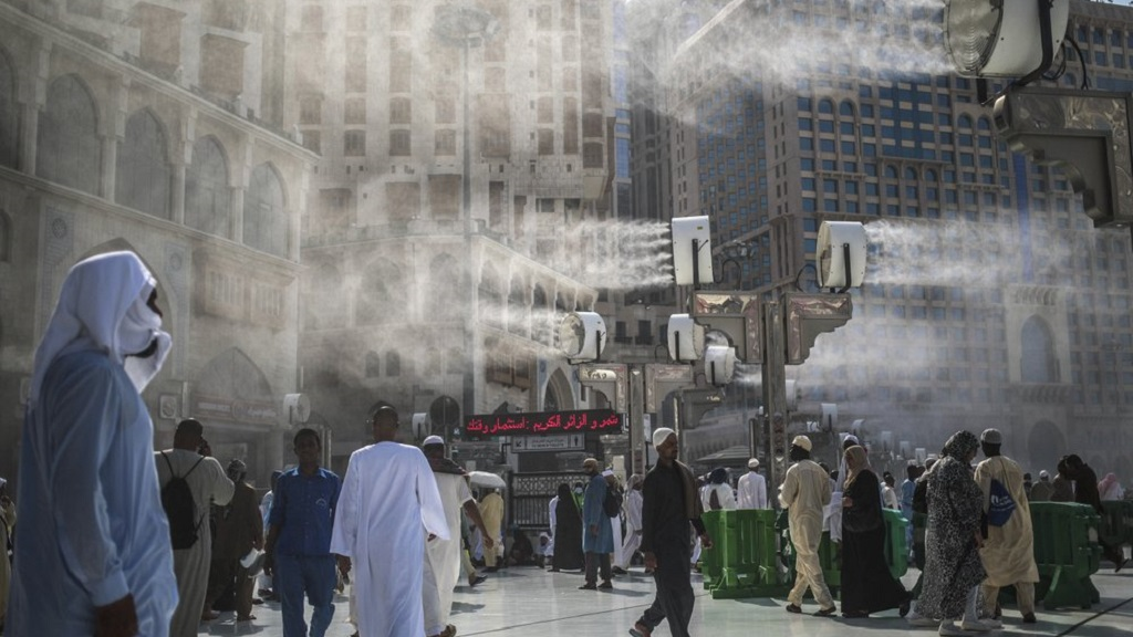 FILE - In this Sept. 15, 2015 file photo, water is sprayed over Muslim pilgrims to cool them down during the afternoon heat as they walk outside the Grand Mosque in the holy city of Mecca, Saudi Arabia. A new study released Monday, May 4, 2020, says 2 to 3.5 billion people in 50 years will be living in a climate that historically has proven just too hot to handle. (AP Photo/Mosa'ab Elshamy, File)
