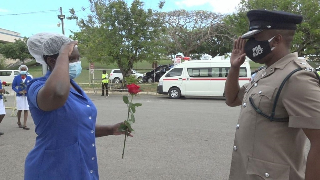 A nurse at the Cornwall Regional Hospital in Montego Bay being saluted by Superintendent Vernon Ellis, commanding officer of the St James Police Division, after she was presented with a rose on Tuesday, which was International Nurses Day 2020.