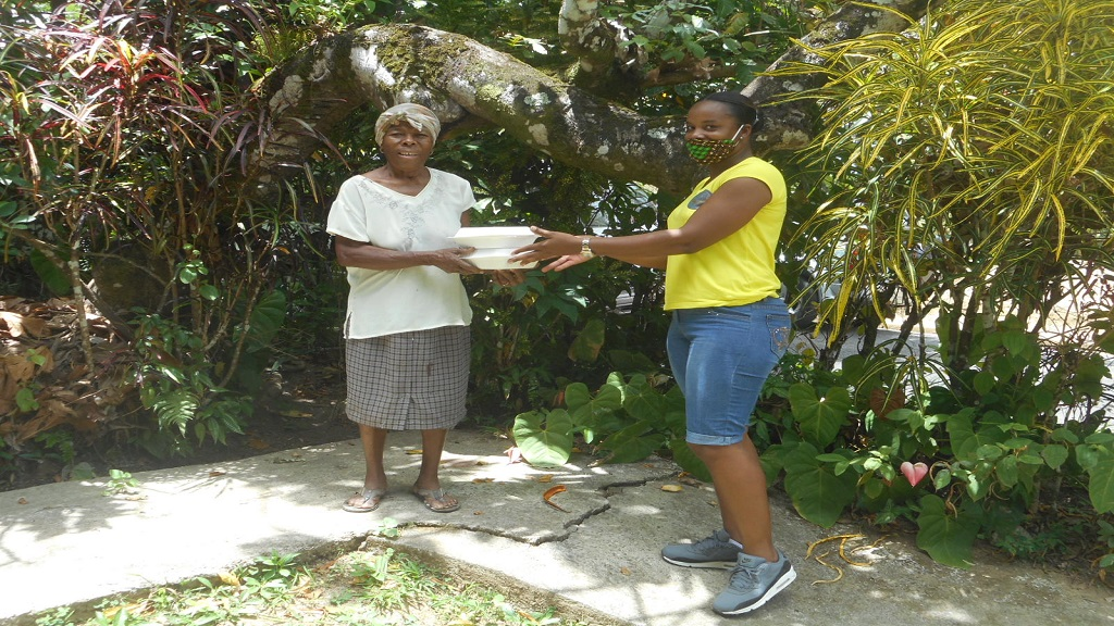 Pauline Auguste receiving her meal from a staff of the Laborie Credit Union