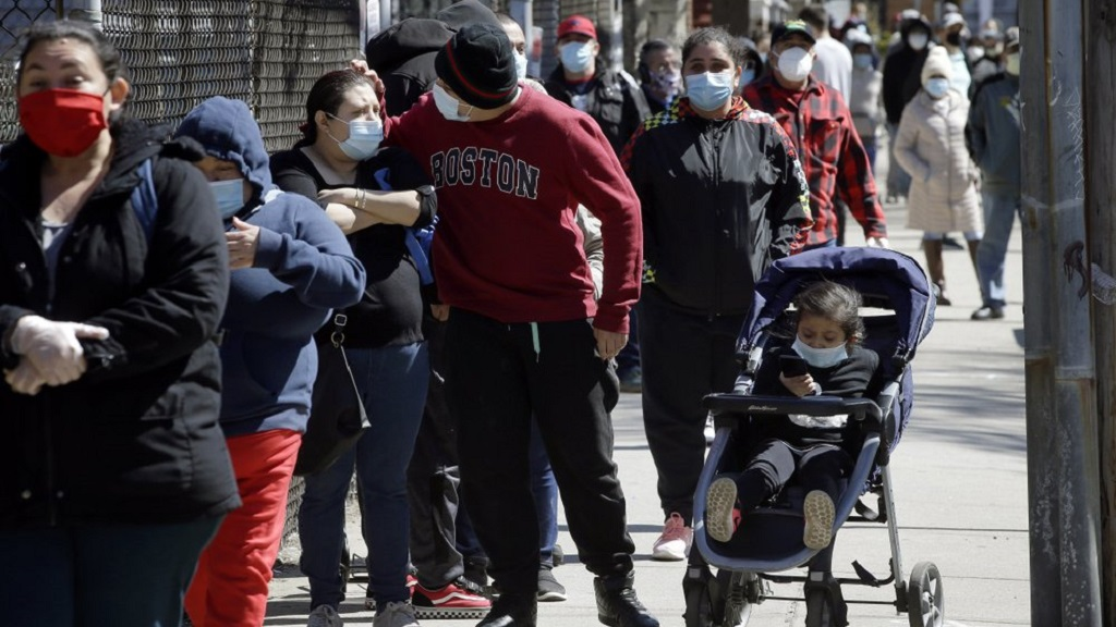 People wear masks out of concern for the coronavirus while standing in line outside a Salvation Army food pantry, Tuesday, May 5, 2020, in Chelsea, Mass. (AP Photo/Steven Senne)