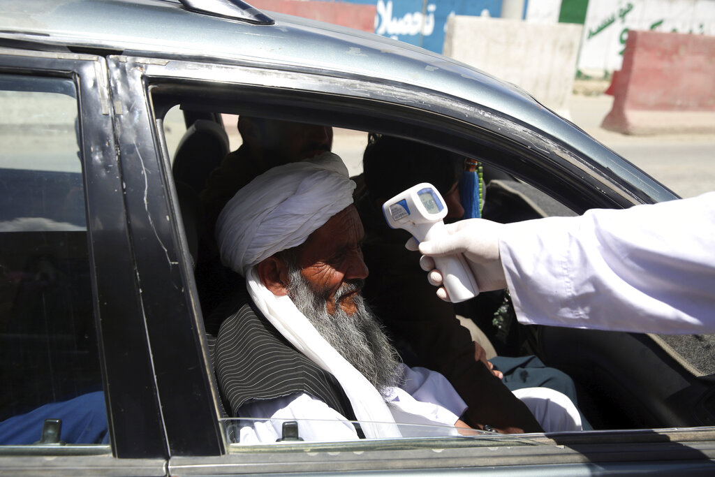 A health worker checks the temperature of car passengers in an effort to prevent the spread of the coronavirus, as they enter the city in the Paghman district of Kabul, Afghanistan, Sunday, May 3, 2020. (AP Photo/Rahmat Gul)