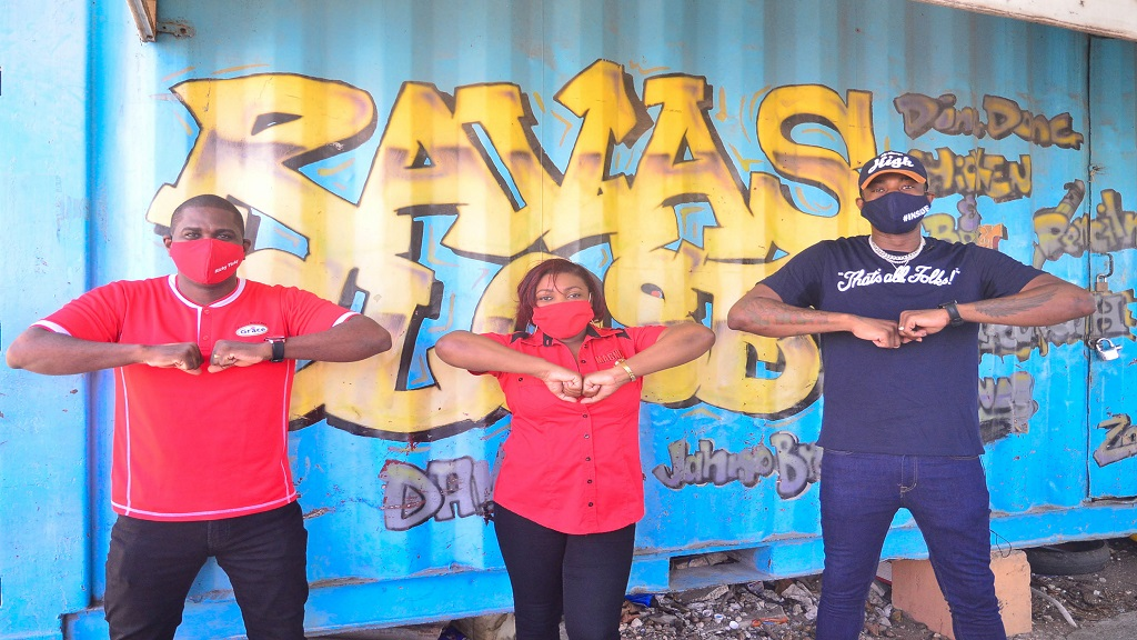 (From left) GraceKennedy's Ricardo Smith, J Wray and Nephew's Marsha Lumley and entertainer Ding Dong touch elbows while posing for the camera during an outreach project in Nannyville on Labour Day.
