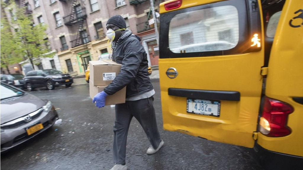 Taxi driver Mor Gob, wearing a mask to protect against coronavirus, delivers boxes with prepared meals to people in need in the Bronx borough of New York, Thursday, April 30, 2020. More than 3.8 million laid-off workers applied for unemployment benefits last week as the U.S. economy slid further into a crisis that is becoming the most devastating since the 1930s. (AP Photo/Mary Altaffer)