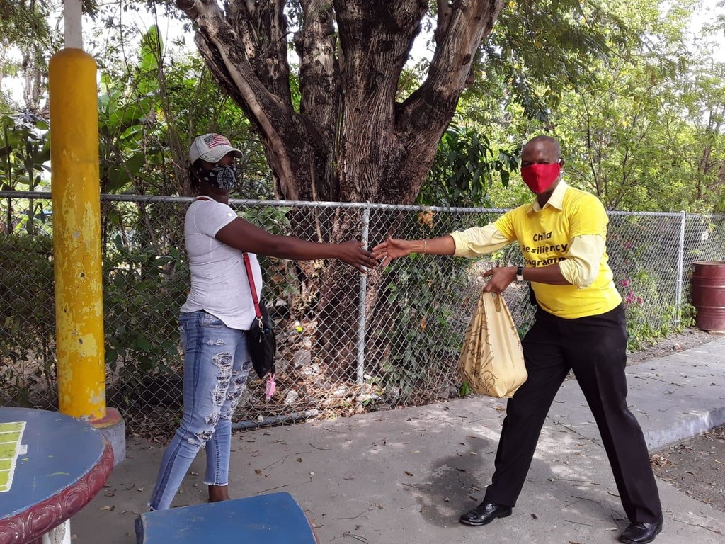Paul Messam (right), coordinator of the Child Resiliency Programme at the Young Men's Christian Association hands over a package to a parent in Kingston.