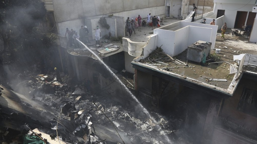 Fire brigade staff try to put out fire caused by plane crash in Karachi, Pakistan, Friday, May 22, 2020. An aviation official says a passenger plane belonging to state-run Pakistan International Airlines carrying more than 100 passengers and crew has crashed near the southern port city of Karachi. There were no immediate reports on the number of casualties. (AP Photo/Fareed Khan)