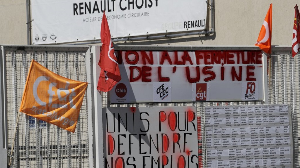 Union flags and poster opposing the closure and job cuts are pictured outside the Renault plant Friday, May 29, 2020 in Choisy-le-Roi, outside Paris. Struggling French carmaker Renault announced 15,000 job cuts worldwide as part of a 2 billion euros cost-cutting plan over three years.  (AP Photo/Christophe Ena)