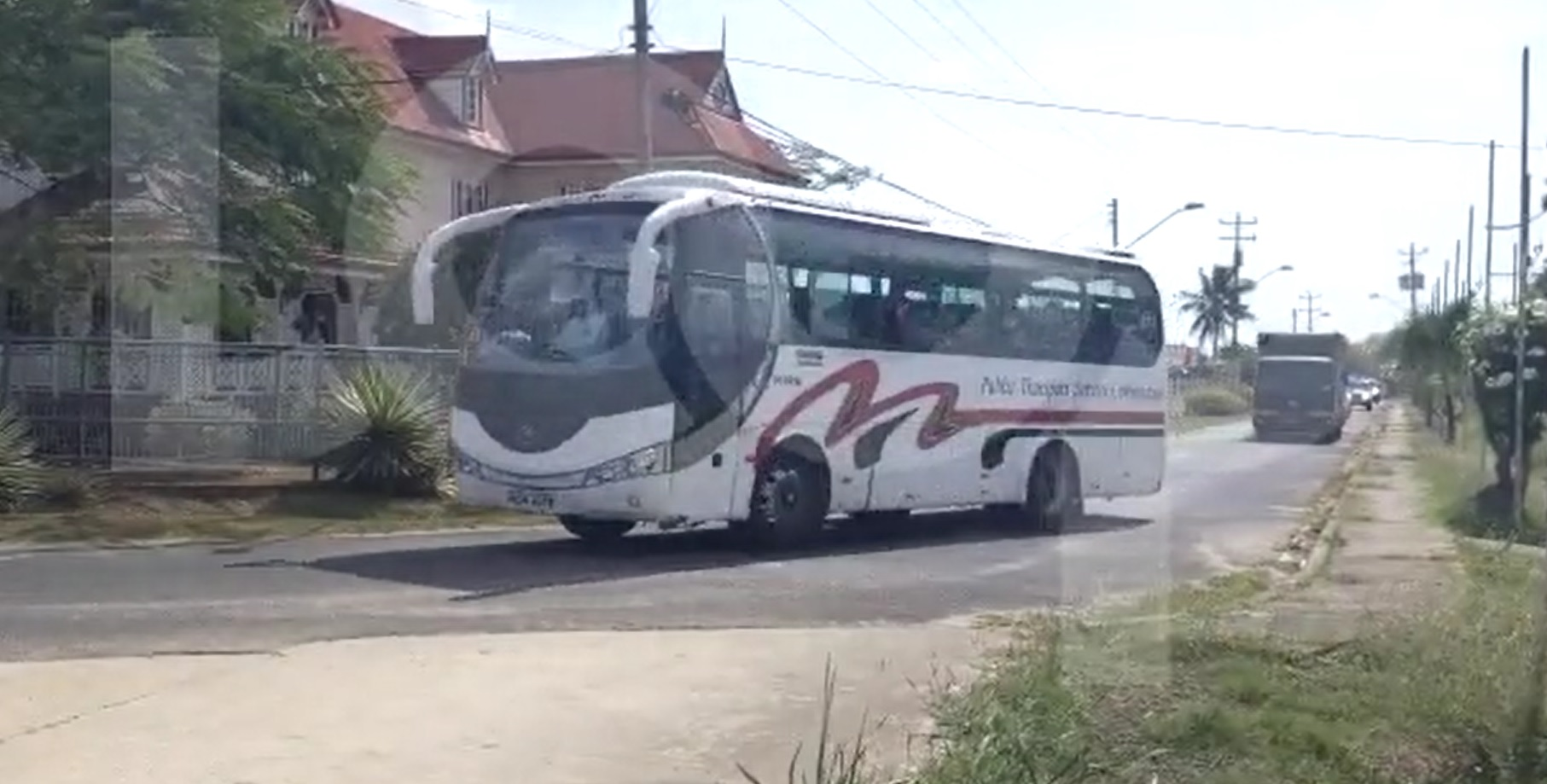 A PTSC bus carrying 33 Trinidadian nationals arrives at the National Racquet Centre.
