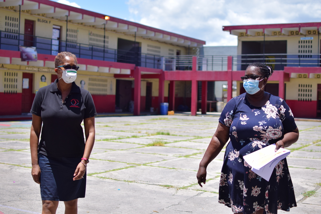 From left: While practising social distancing, Stephannie Coy, Project Manager of the Desnoes and Geddes (D&G) Foundation, discusses school closure with Brendalee Mclaughlin, the Grade One Coordinator and Special-Needs Instructor at the Seaview Gardens Primary and Junior High.