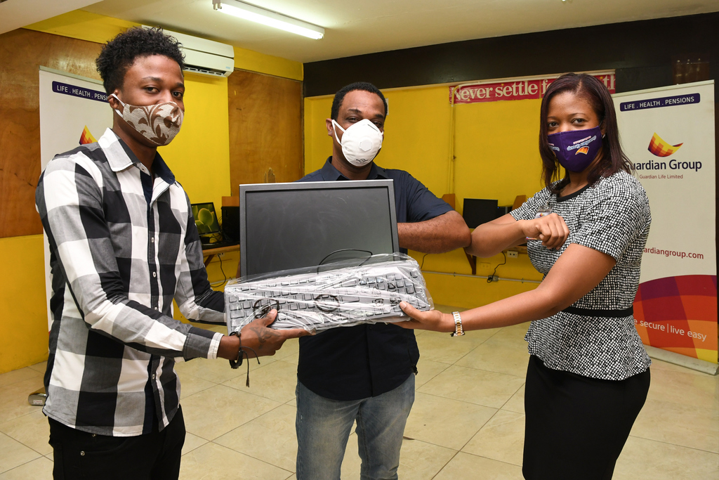 Ackelie Burrell (left),  Mathematics & Exam Coordinator at Charlie Smith High School and Anthony Garwood (centre), Principal, Charlie Smith High School receive computer equipment valued at $1 million from Kelsa-Marie Pinnock-Daubon (right), Vice President - Information Technology, Guardian Life Limited.