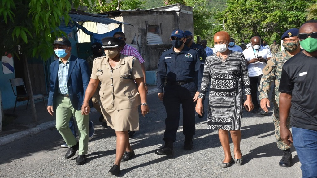 National Security Minister, Dr Horace Chang (left foreground), along with Science, Energy and Technology Minister and Eastern St Andrew Member of Parliament (MP), Fayval Williams (centre), along with representatives of the security forces, on a visit to August Town on Sunday.