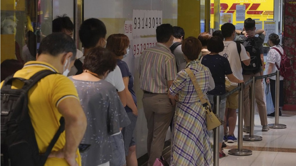People queue up outside the DHL Express store in Hong Kong, Monday, June 1, 2020. Throngs of people lined up at DHL courier outlets across the city on Monday, many to send documents to the U.K. to apply for or renew what is known as a British National (Overseas) passport. (AP Photo/Vincent Yu)