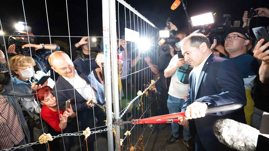(Friday, June 12, 2020) Lord Mayor of Gorlitz Octavian Ursu, center right, and Mayor of Zgorzelec, Poland, Rafal Gronicz, center left, together open the border fence on the Gorlitz Old Town Bridge in Gorlitz, Germany. Europe is taking a big step toward a new normality after the coronavirus outbreak as many countries open up their borders to fellow Europeans – but exceptions remain, and it remains to be seen how many will use their rediscovered freedom to travel. (Daniel Schafer/dpa via AP, file)