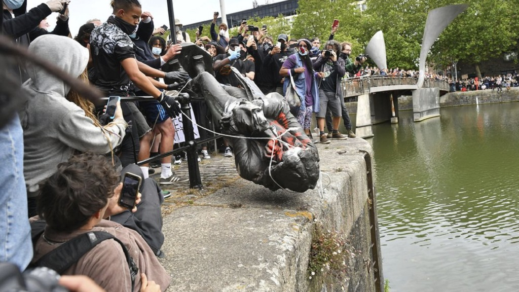 Protesters throw a statue of slave trader Edward Colston into Bristol harbour during a Black Lives Matter protest rally, in Bristol, England, Sunday June 7, 2020, in response to the recent killing of George Floyd by police officers in Minneapolis, USA, that has led to protests in many countries and across the US. (Ben Birchall/PA via AP)
