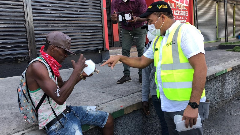 Health Minister Dr Christopher Tufton (right) talks to a man after handing out one of thousands of masks in HWT on Monday.