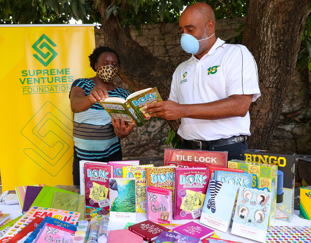 Supreme Ventures' Xesus Johnston, CEO of the Prime Sports Jamaica Limited subsidiary, presents books and other items to Karlene Small, a caregiver at the Elsie Bemand Home for Girls in Meadowbrook, St Andrew.