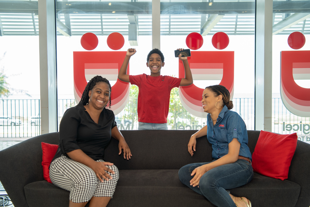 Eleven-year-old millionaire D'Jaughn Brown pumps his fists in excitement in response to being named winner of the weekly grand prize of $1 million + $200,000 to charity in the Digicel Shake Win and Donate promotion. Sharing the moment is his mom, Sandrina Davis (left), and Digicel Jamaica Brand Marketing Manager, Ayanna Kirton.
