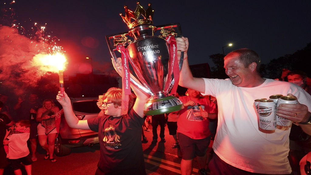Liverpool supporters hold a replica Premier League trophy as they celebrate outside of Anfield Stadium in Liverpool, England, Thursday, June 25, 2020. Liverpool clinched the title after Manchester City failed to beat Chelsea on the day. (AP photo/Jon Super).