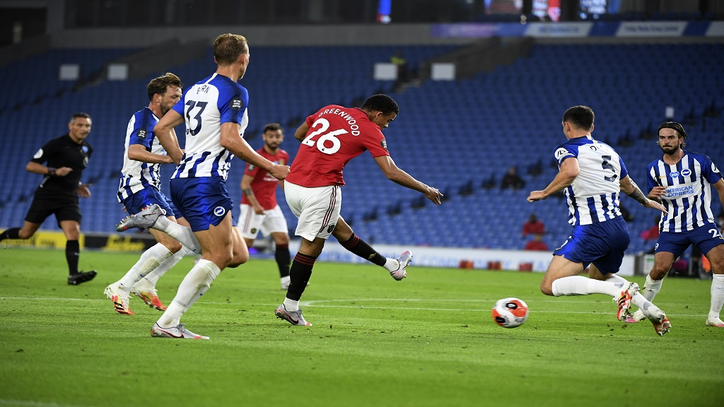 Manchester United's Mason Greenwood, centre, scores the opening goal for his team during the English Premier League football match against Brighton at the AMEX Stadium in Brighton, England, Tuesday, June 30, 2020. (Andy Rain/Pool via AP).