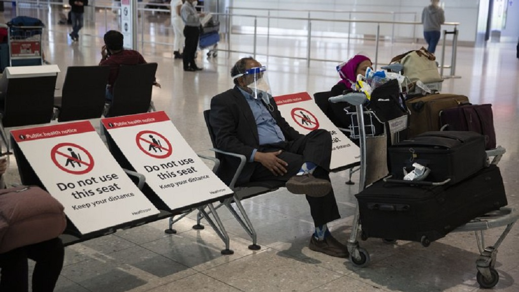 A man sits wearing a face shield in the arrivals area on the first day of new rules that people arriving in Britain from overseas will have to quarantine themselves for 14 days to help stop the spread of coronavirus, at Heathrow Airpot in London, Monday, June 8, 2020. The British government has said that anyone caught not complying with the quarantine will face a fine. (AP Photo/Matt Dunham)