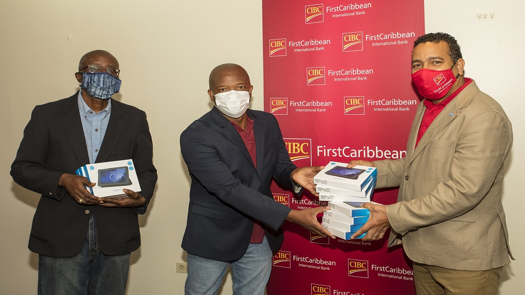 CIBC FirstCaribbean International Bank Managing Director, Nigel Holness (right) presents some of the tablets to Donovan Betancourt (centre), President of the school's Alumni Association and Fred Sutherland, Immediate past president.