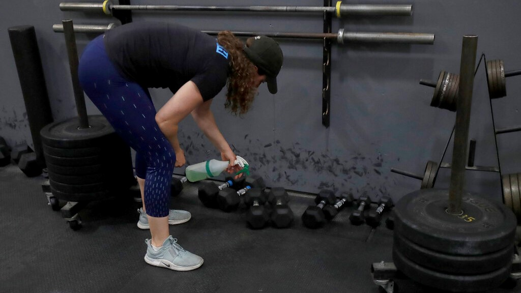 In a Friday, April 24, 2020 file photo, Alexis Garrod, CrossFit Potrero Hill partner and head coach, cleans off weight training equipment in an empty gym, which closed for shelter in place orders over COVID-19 concerns, in San Francisco. (AP Photo/Jeff Chiu, File)
