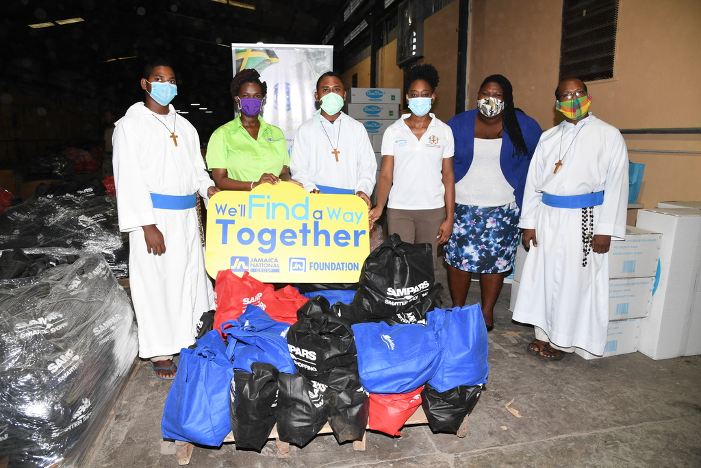 Onyka Barrett Scott (second left), general manager of JN Foundation and her team Zola Hinds (third right), corporate social responsibility officer and Chevanese Peters (second right), programmes coordinator at the JN Foundation present care packages to Elijah Kujur Mop (right), Simran Barla (left) and Lorianus Kollo,  representatives of Missionaries of the Poor.