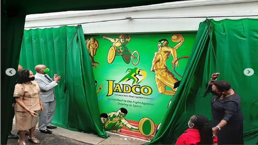 Sport Minister Olivia Grange (right) and JADCO's  Chairman Alexander Williams unveil the JADCO mural wall during the official opening of the commission's new headquarters at 1 Ballater Avenue in Kingston on June 11, 2020. Executive Director of JADCO, June Spence-Jarrett (first left) and Paralympian Alphanso Cunningham (first right) share in the occasion.