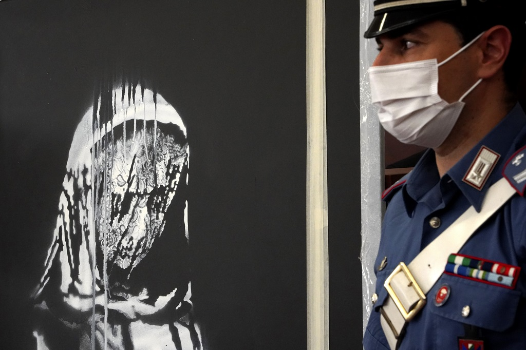 Italian authorities unveil a stolen artwork painted by the British artist Banksy as a tribute to the victims of the 2015 terror attacks at the Bataclan music hall in Paris, during a press conference in L' Aquila, Italy,  June 11, 2020 . The L'Aquila prosecutors office said the work was recovered on Wednesday during a search of a home in Tortoreto, a city near the Adriatic coast in the Abruzzo region's Teramo province. (AP Photo/Andrea Rosa)