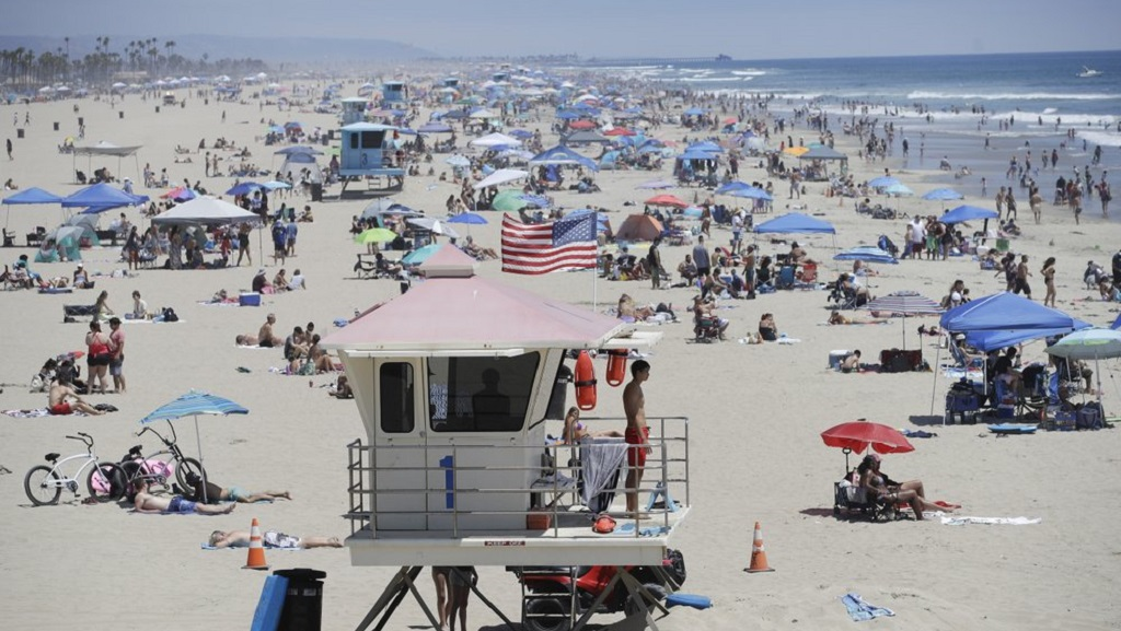 Photo: A lifeguard keeps watch over a packed beach Saturday, June 27, 2020, in Huntington Beach, Calif. (AP Photo/Marcio Jose Sanchez)