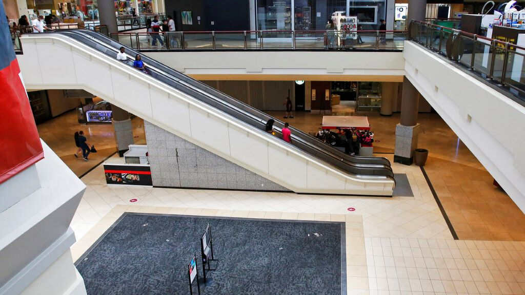 FILE - In this May 1, 2020, file photo, people ride down an escalator at a shopping mall in Oklahoma City as it reopens from its closure since mid-March due to coronavirus concerns. (AP Photo/Sue Ogrocki, File)