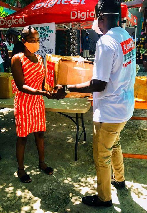 Un agent de la Digicel remettant un kit à une habitante de Hinche. Photo: Digicel Haiti