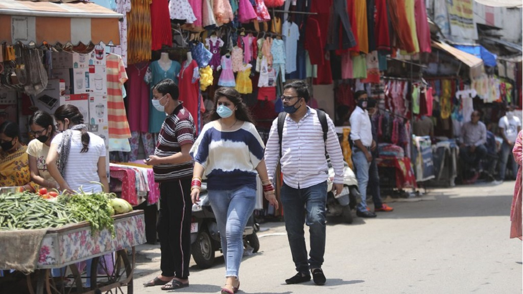 Indian commuters wear masks and walk at a market in Jammu, India, Sunday, June 7, 2020. India whose coronavirus caseload is fifth highest in the world has partially restored trains and domestic flights and allowed reopening of shops and manufacturing. (AP Photo/Channi Anand)