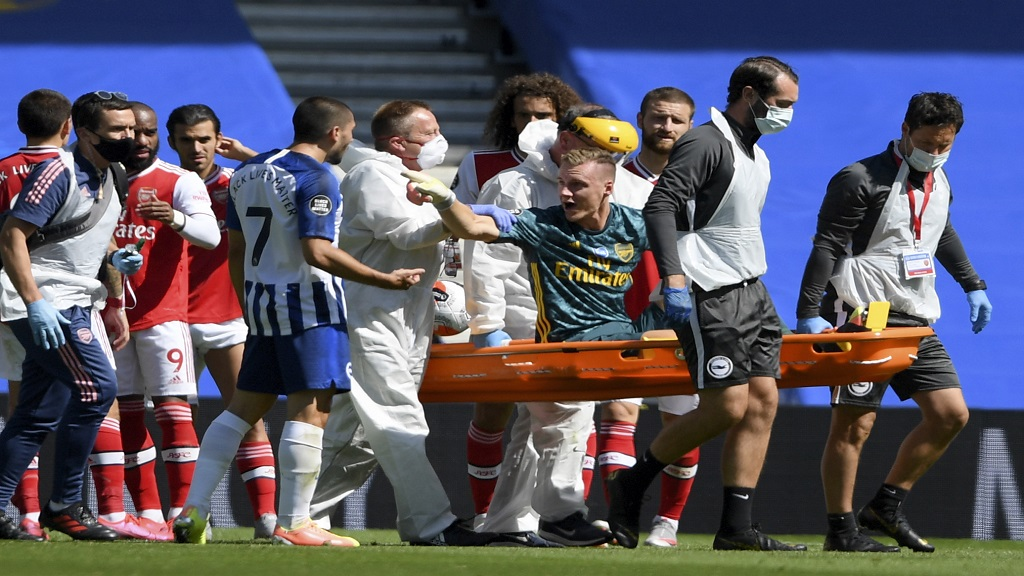 Arsenal's goalkeeper Bernd Leno gestures at Brighton's Neal Maupay as he leaves the pitch on a stretcher after getting injured during their English Premier League football match at the AMEX Stadium in Brighton, England, Saturday, June 20, 2020. (Mike Hewitt/Pool via AP).