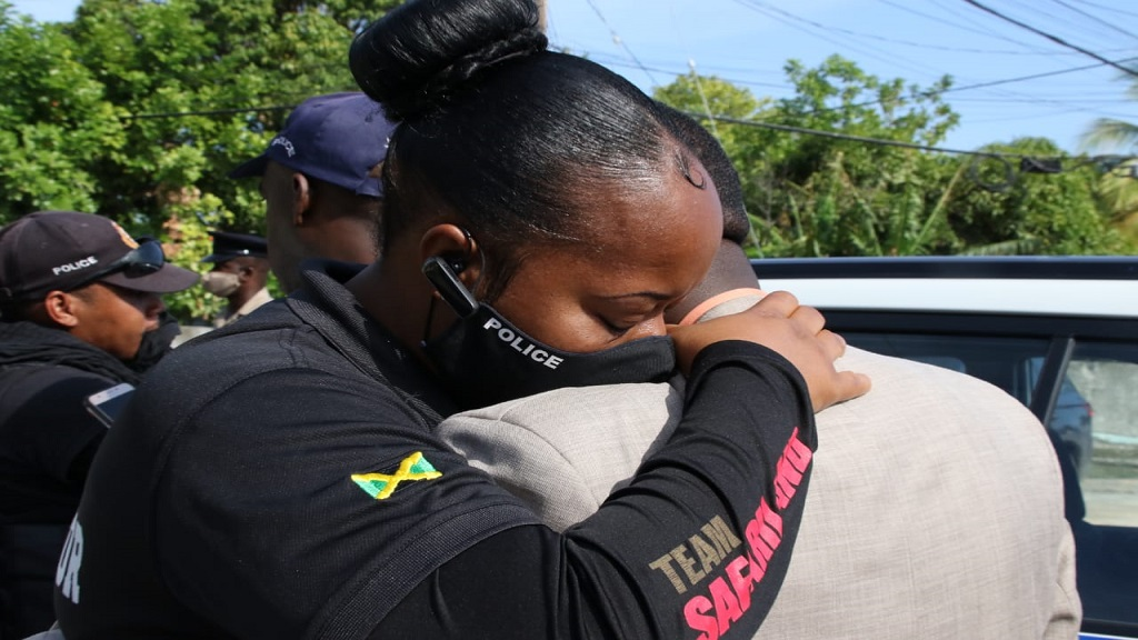 A policewoman embraces a colleague following the fatal attack on a group of police officers in St Catherine on Friday morning.