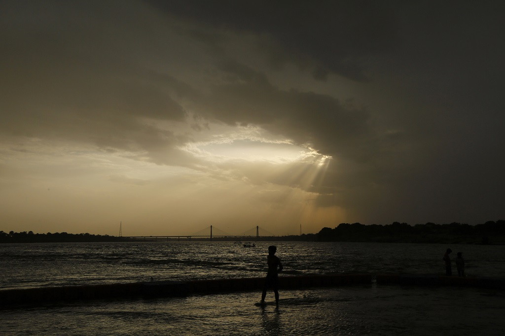FILE - In this Wednesday, May 27, 2020 file photo, a boy stands on the shore of the Ganges River during a hot summer day in Prayagraj, India.  (AP Photo/Rajesh Kumar Singh)