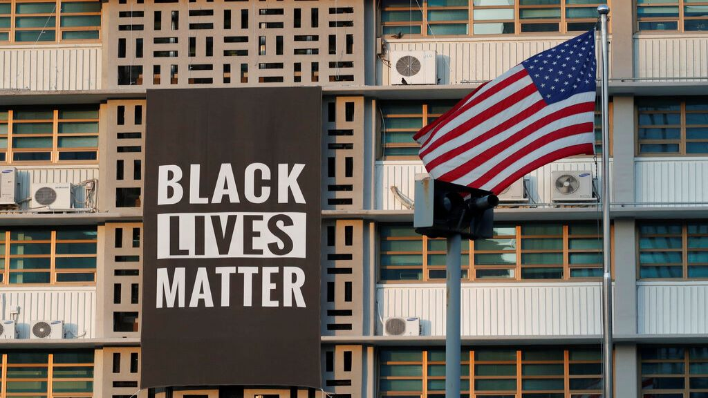 In this June 14, 2020 photo, US flag flutters next to a giant Black Lives Matter banner at the US Embassy in Seoul, South Korea. (AP Photo/Lee Jin-man)
