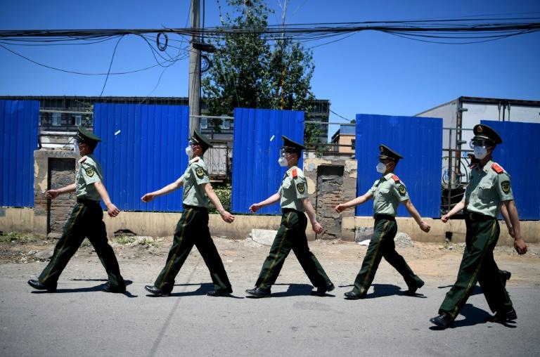 La police paramilitaire chinoise passe devant le marché Xinfadi, le 14 juin 2020 à Pékin fermé après la détection de nouveaux cas de coronavirus