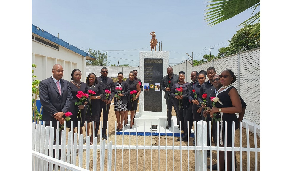 PoliceFederation members stand beside a monument erected in honour of the two policemen - 32-year-old Detective Corporal Dane Biggs and 26-year-old Constable Decardo Hylton - who were killed in an early morning operation in Horizon Park, on Friday, June 12.