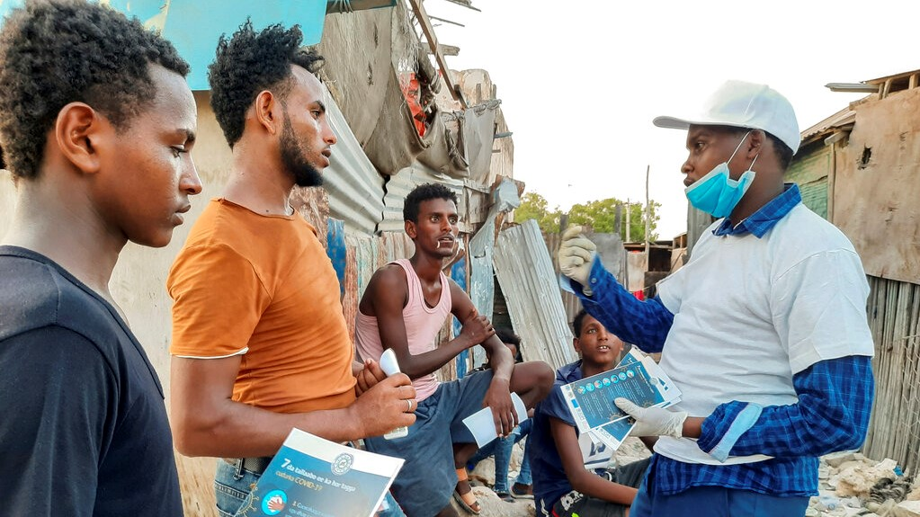 In this photo taken Wednesday, May 20, 2020, stranded Ethiopian migrants receive informational materials informing them how to protect themselves against the coronavirus, in Bosaso, Somalia. (International Organisation for Migration (IOM) - Somalia via AP)