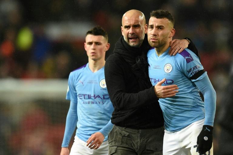 L'entraîneur de Manchester City Pep Guardiola conseille Nicolas Otamendi lors d'un match de Premier League face à Manchester United, à Old Trafford, le 8 mars 2020