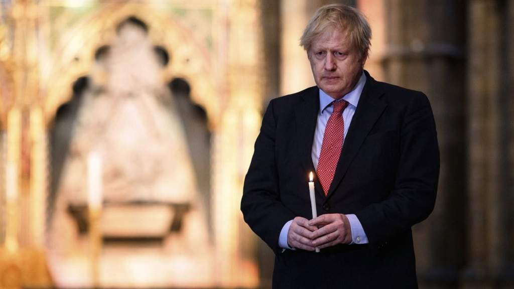 Britain's Prime Minister Boris Johnson prepares to light a candle at the Grave of the Unknown Warrior in Westminster Abbey in London, Thursday May 7, 2020, ahead of commemorations to mark the 75th anniversary of VE Day on Friday. (Leon Neal/Pool via AP)