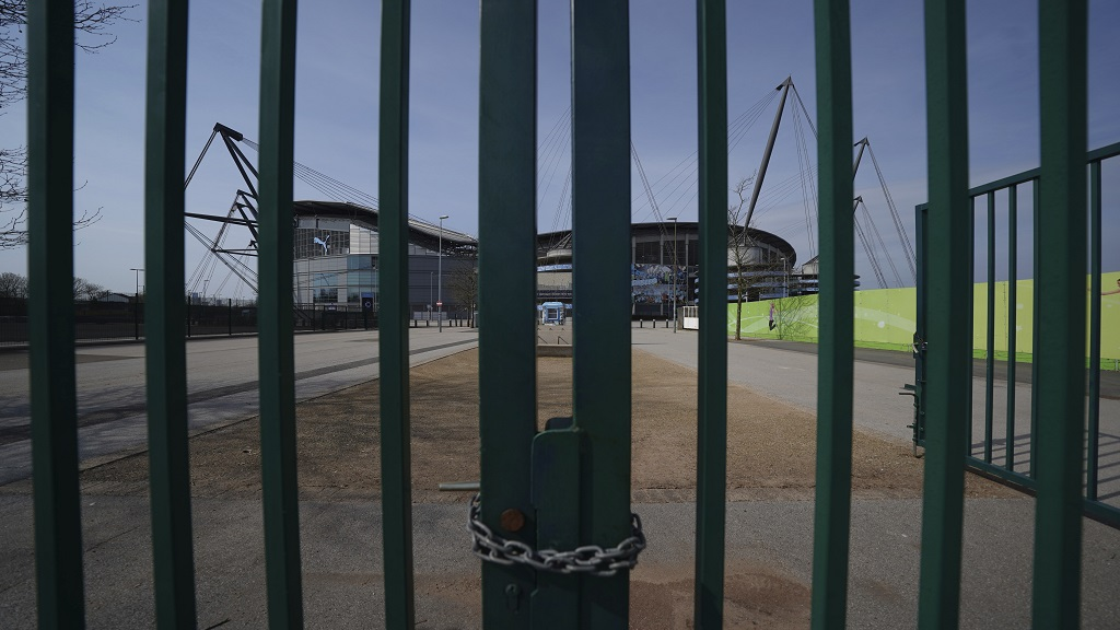 In this file photo dated Thursday, April 9, 2020, gates stand locked outside the closed Manchester City Etihad Stadium, in Manchester, northern England. Guidance for sports bodies was published by the government on Saturday May 30, 2020, as COVID-19 lockdown restrictions are being eased further, allowing Sports events to resume in England from upcoming Monday, without any spectators. (AP Photo/Jon Super).