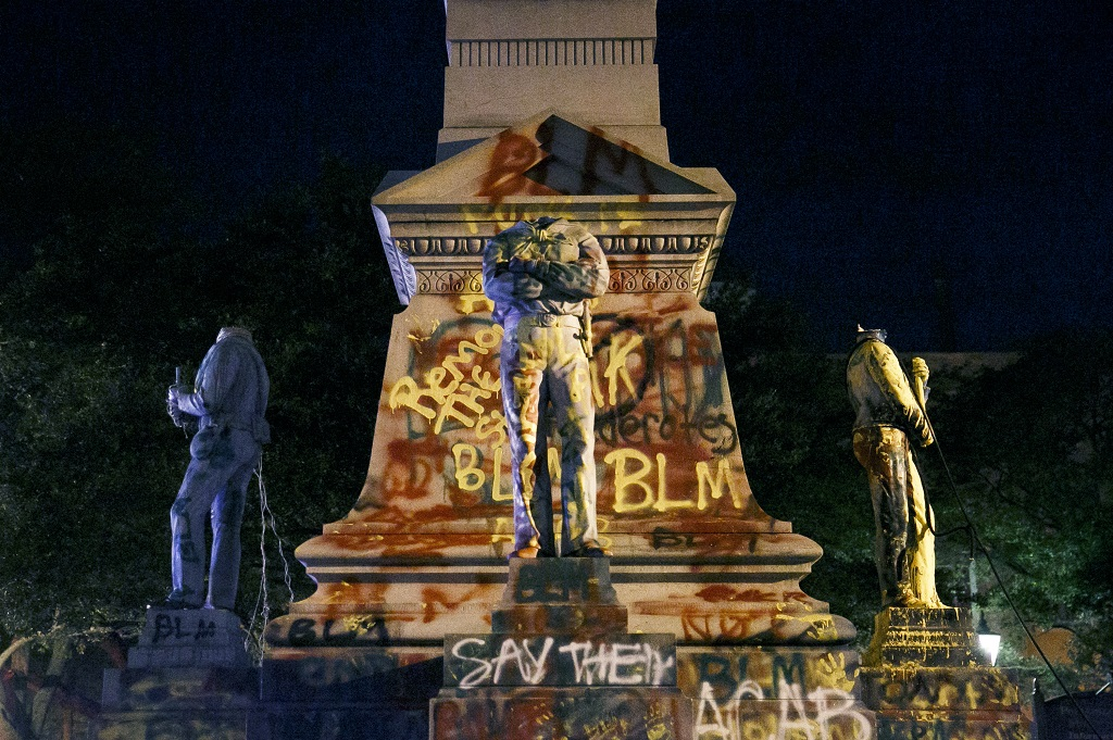 The statues on the Confederate monument are covered in graffiti and beheaded after a protest in Portsmouth, Virginia on June 10, 2020. Protesters beheaded and then pulled down four statues that were part of a Confederate monument. The crowd was frustrated by the Portsmouth City Council's decision to put off moving the monument. (Kristen Zeis/The Virginian-Pilot via AP)