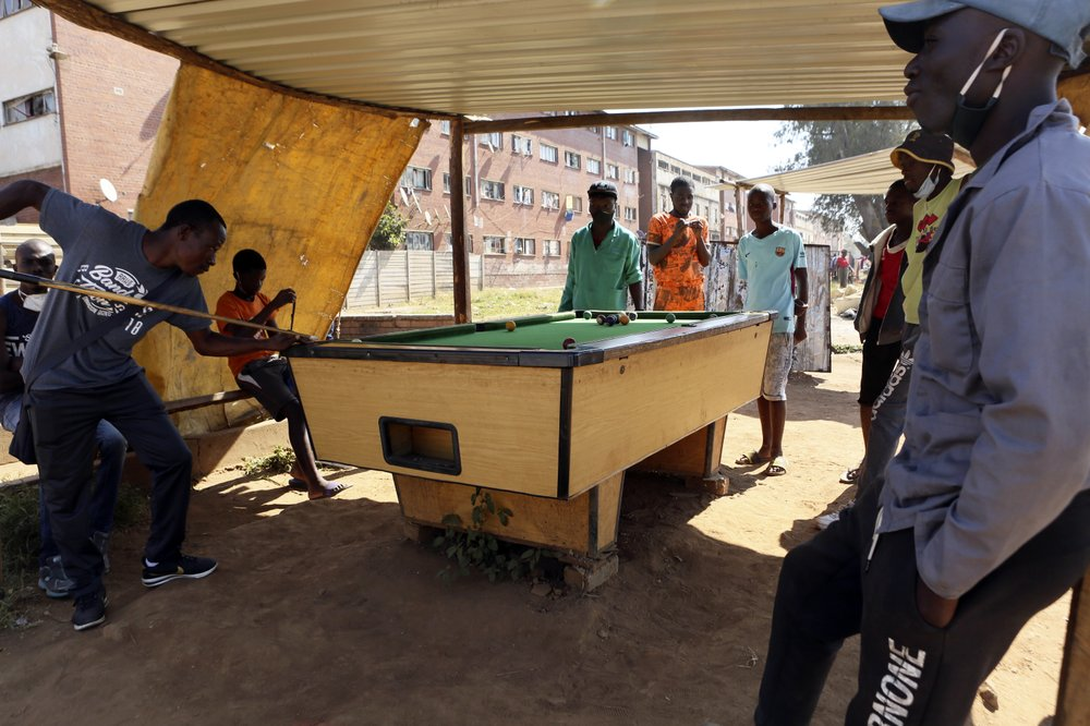 A group play a game of pool in the poor Mbare suburb in the capital Harare. (AP Photo/Tsvangirayi Mukwazhi)