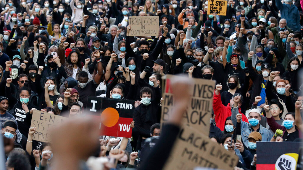Protesters gather in Sydney, Saturday, June 6, 2020, to support the cause of US protests over the death of George Floyd. Black Lives Matter protests across Australia proceeded mostly peacefully as thousands of demonstrators in state capitals honored the memory of Floyd and protested the deaths of indigenous Australians in custody. (AP Photo/Rick Rycroft)