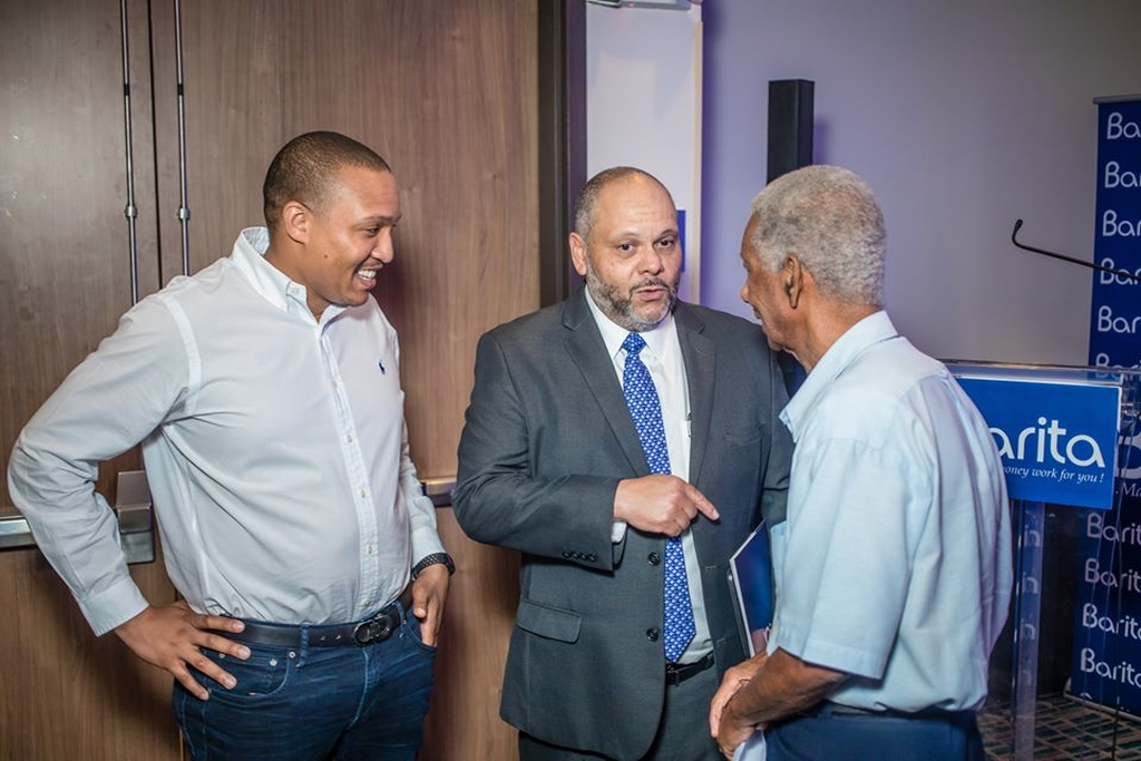 Chairman of Barita Investments Mark Myers (centre), deputy chairman Paul Simpson (left) speak to shareholder Orette Staple following an annual general meeting.