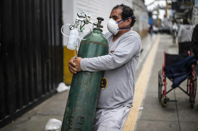 Un homme porte une bouteille d'oxygène à un proche, hospitalisé au Mayo Hospital à Lima, Pérou, le 3 juin 2020