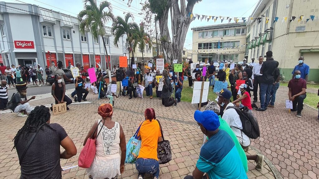 Protesters kneel at the Black Lives Matter protest at Constitution Park in Castries