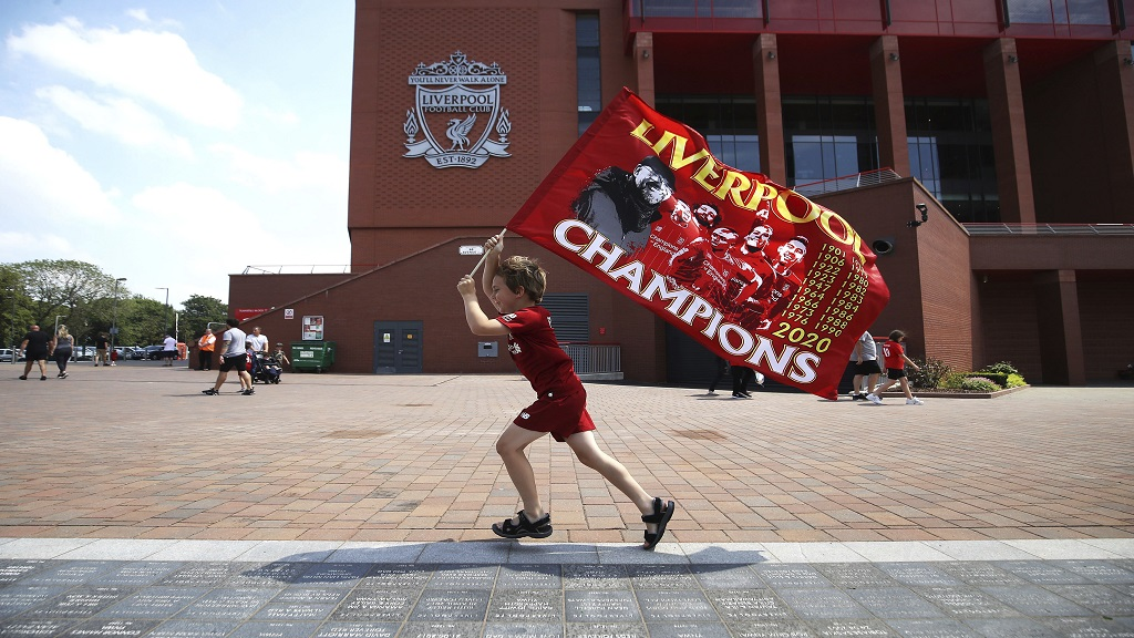 Liverpool fan Dillon Parry waves a flag outside Anfield in Liverpool, England, Friday June 26, 2020. Liverpool clinched their first league title since 1990 on Thursday, ending an agonising title drought. (Martin Rickett/PA via AP).