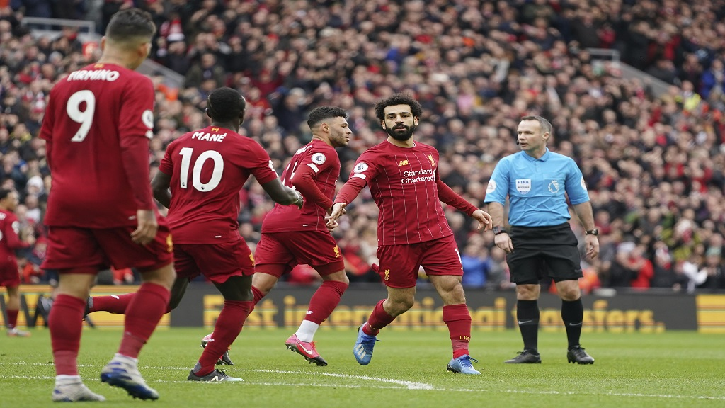 Liverpool's Mohamed Salah, right, celebrates with his teammates after scoring his side's opening goal during the English Premier League football match against Bournemouth at Anfield stadium in Liverpool, England, Saturday, March 7, 2020. (AP Photo/Jon Super).
